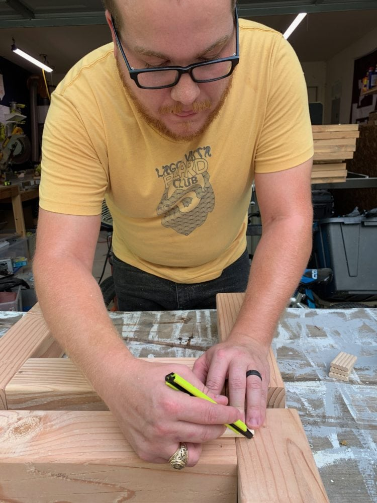 man assembling legs for an outdoor coffee table