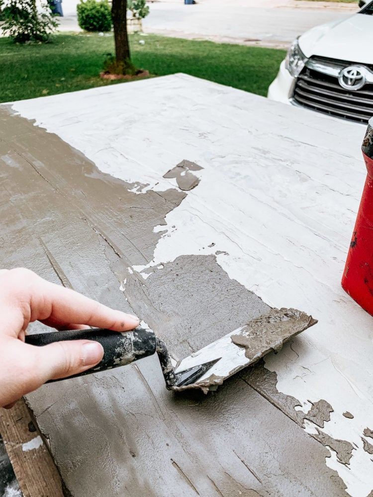 hand applying concrete feather finish to a table top