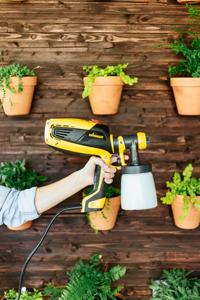 woman's hand holding a paint sprayer in front of a DIY plant wall