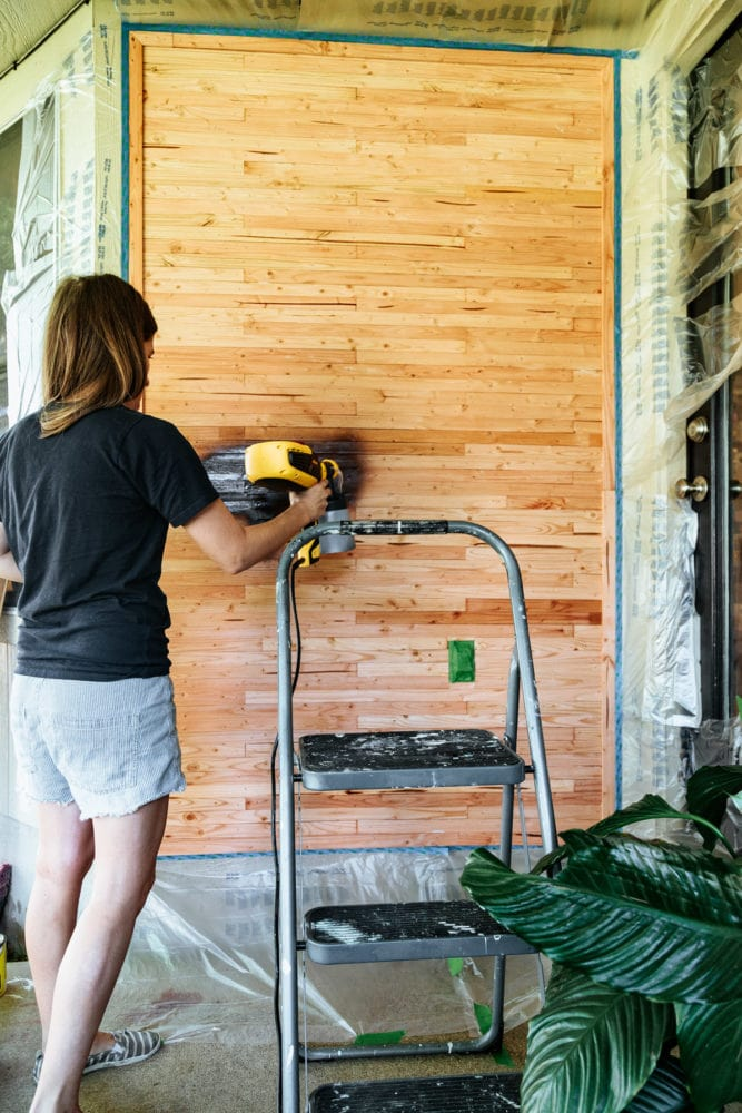 woman staining a wall with a paint sprayer