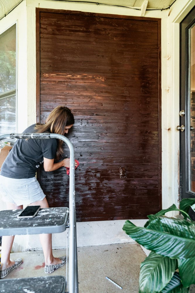 woman staining an outdoor plant wall