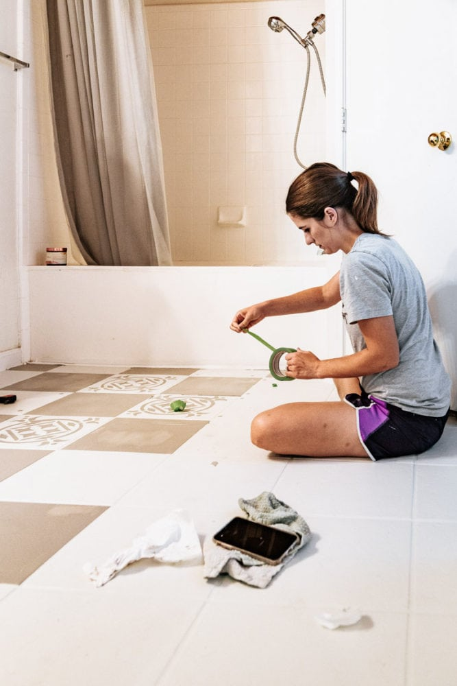 woman taping off flooring to create a checkboard pattern on tile floor