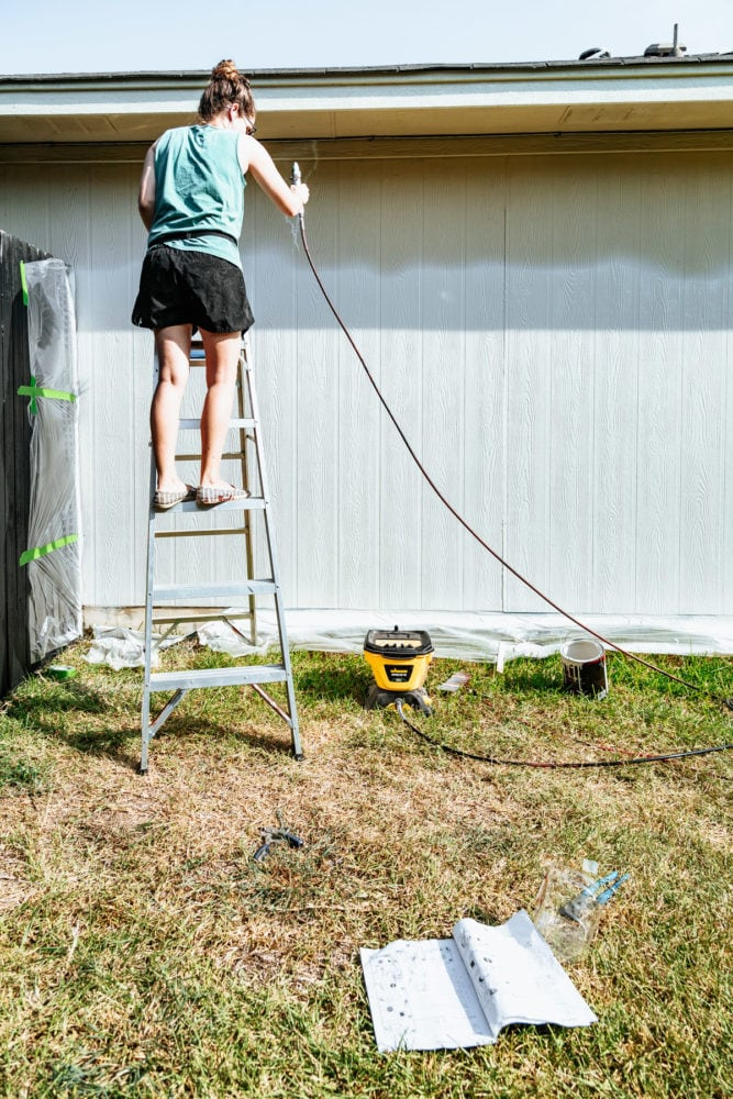 woman using a paint sprayer to paint the exterior of a house