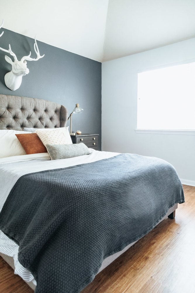 a master bedroom with blue and white walls and wood flooring