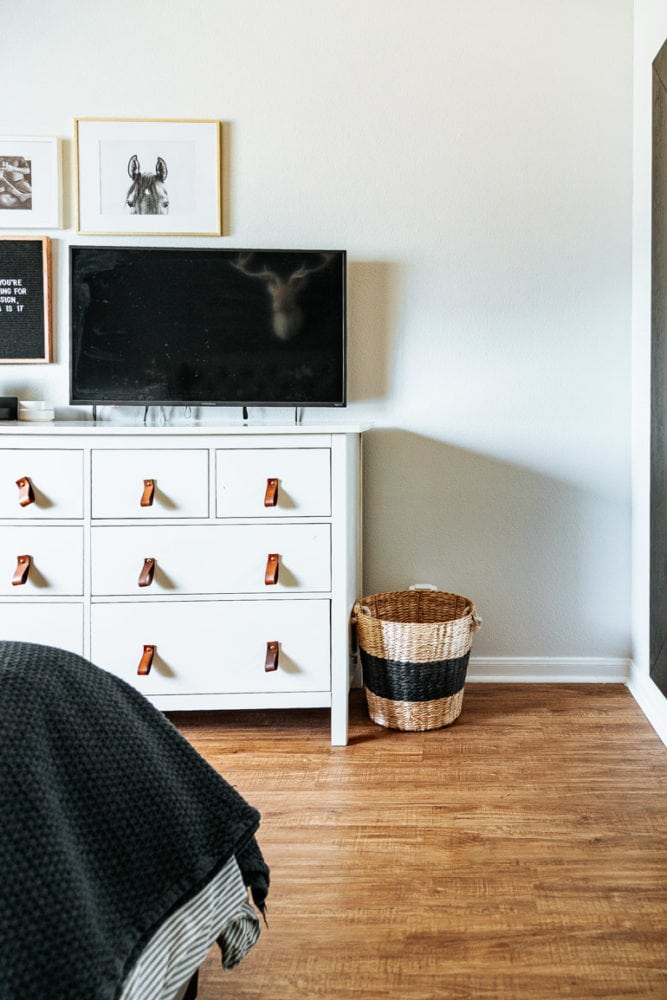a corner of a master bedroom with white walls