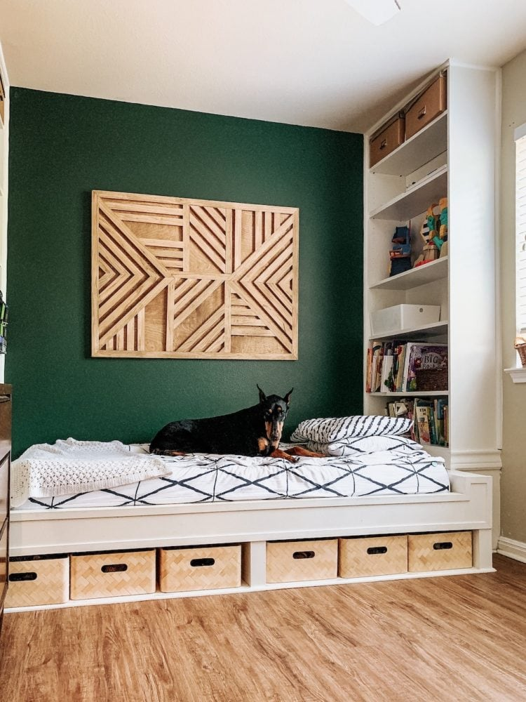 A kids' bedroom with a built-in bed and a green wall