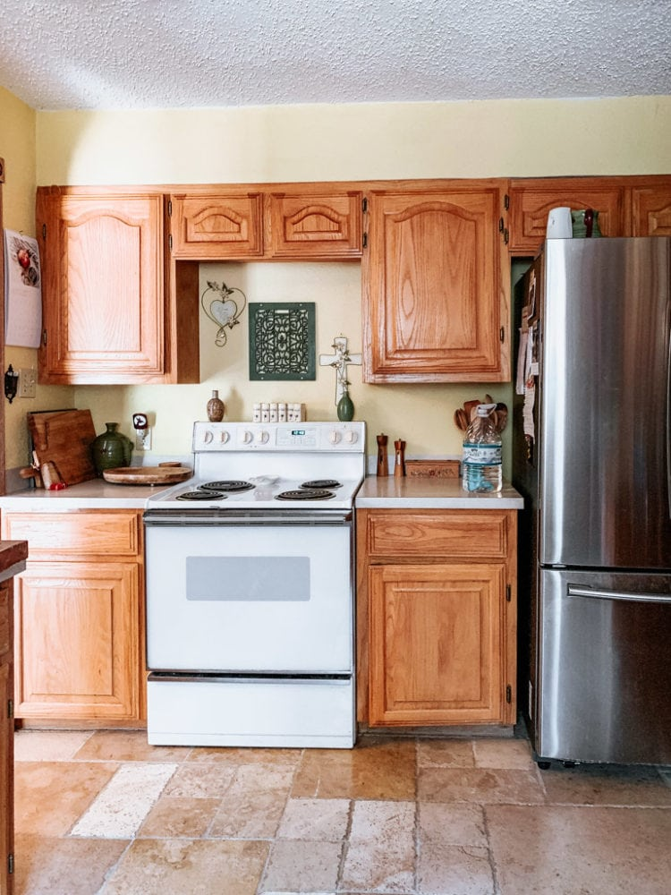 dated kitchen with light cabinetry and yellow walls