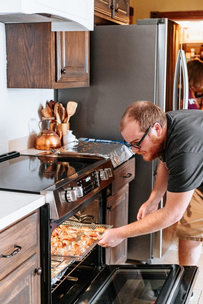 man placing chicken wings into range to be air fried