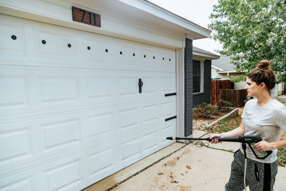 woman using a pressure washer to clean a garage door