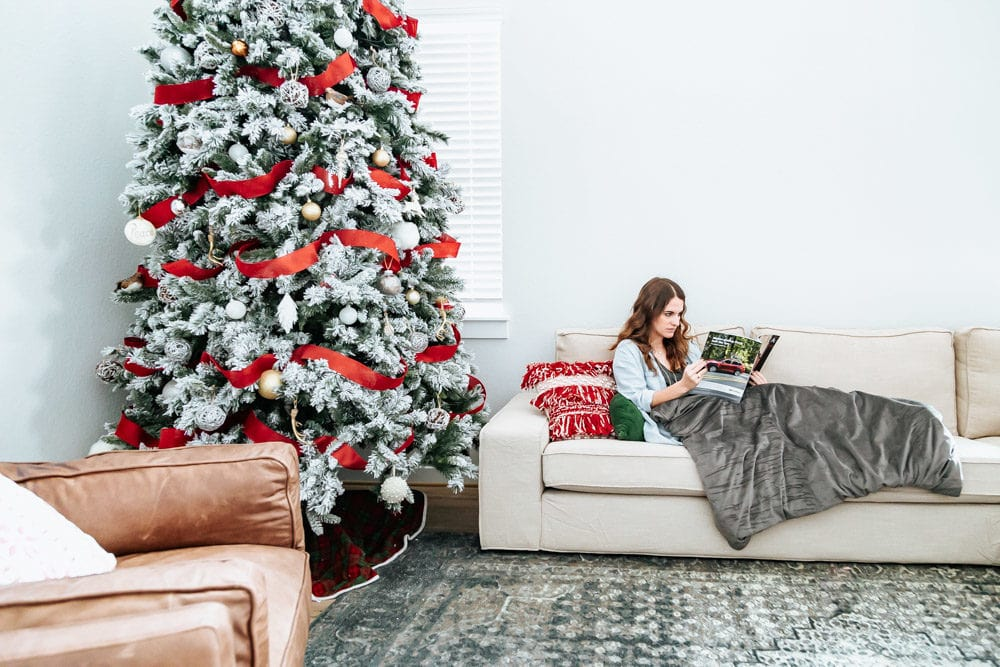 woman sitting on a large couch next to a Christmas tree with a weighted blanket