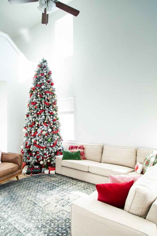 A living room with a large christmas tree