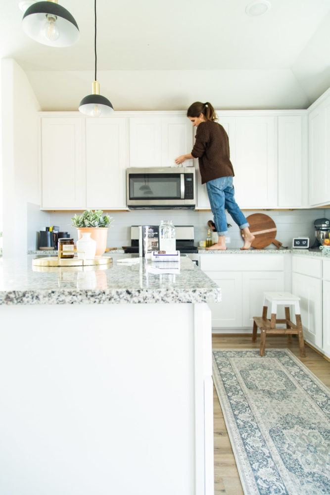 woman cleaning white kitchen cabinets
