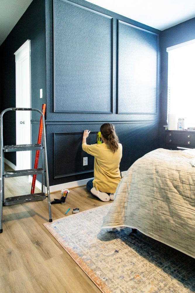 woman using a pin nailer on picture molding trim