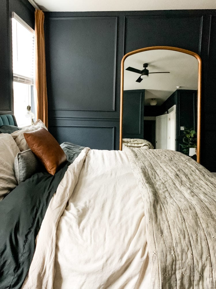 dark blue bedroom with a large mirror and gold curtains