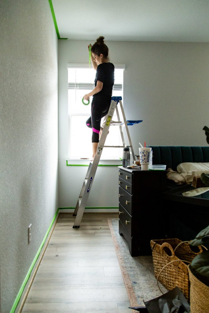woman using painter's tape to prep for painting a room