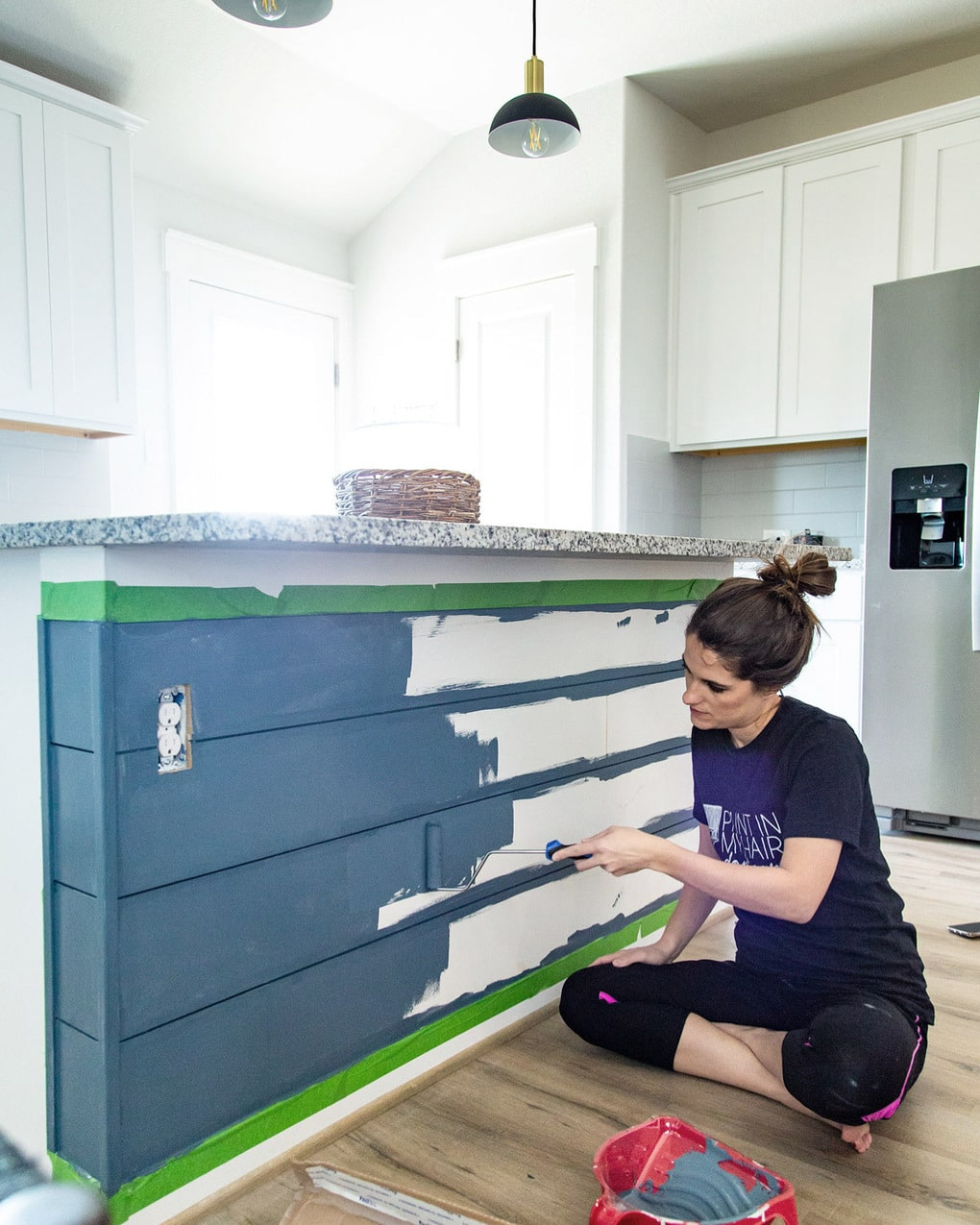 woman painting a kitchen island