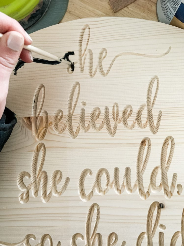 woman's hand painting detailed letters on a wood carved sign