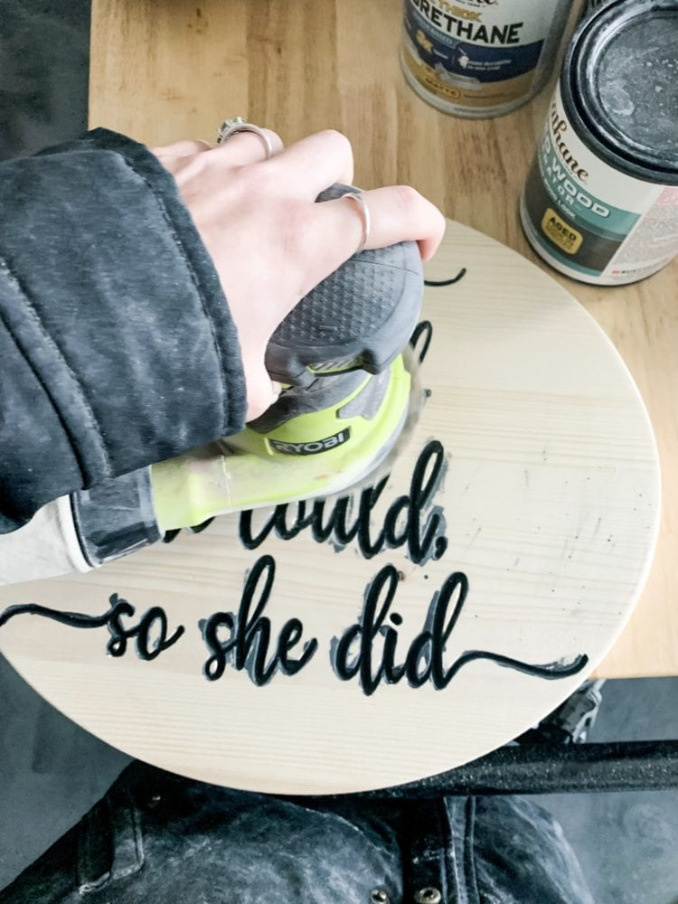 woman's hand sanding a wood carved sign
