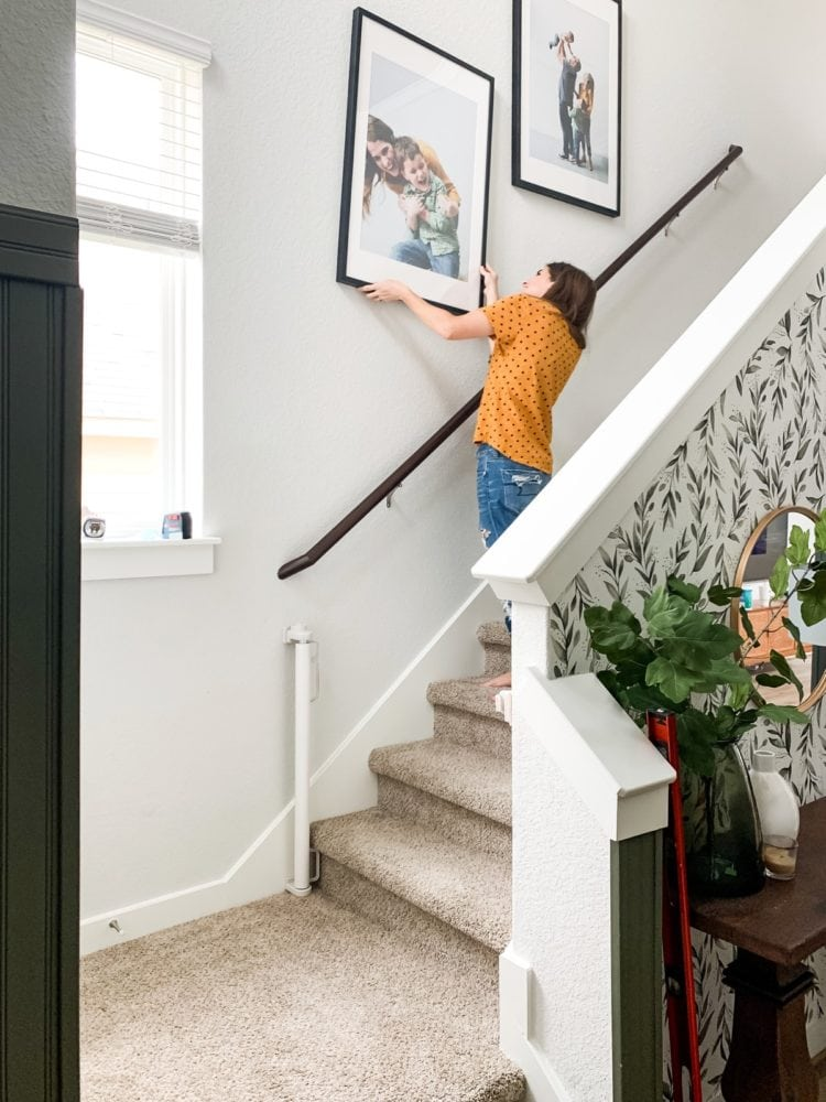 Woman hanging a large frame on her stair wall