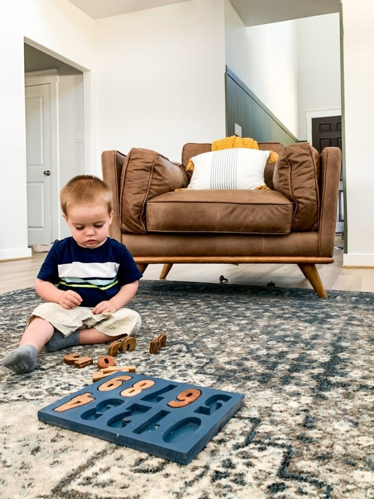 toddler playing with a DIY wood puzzle