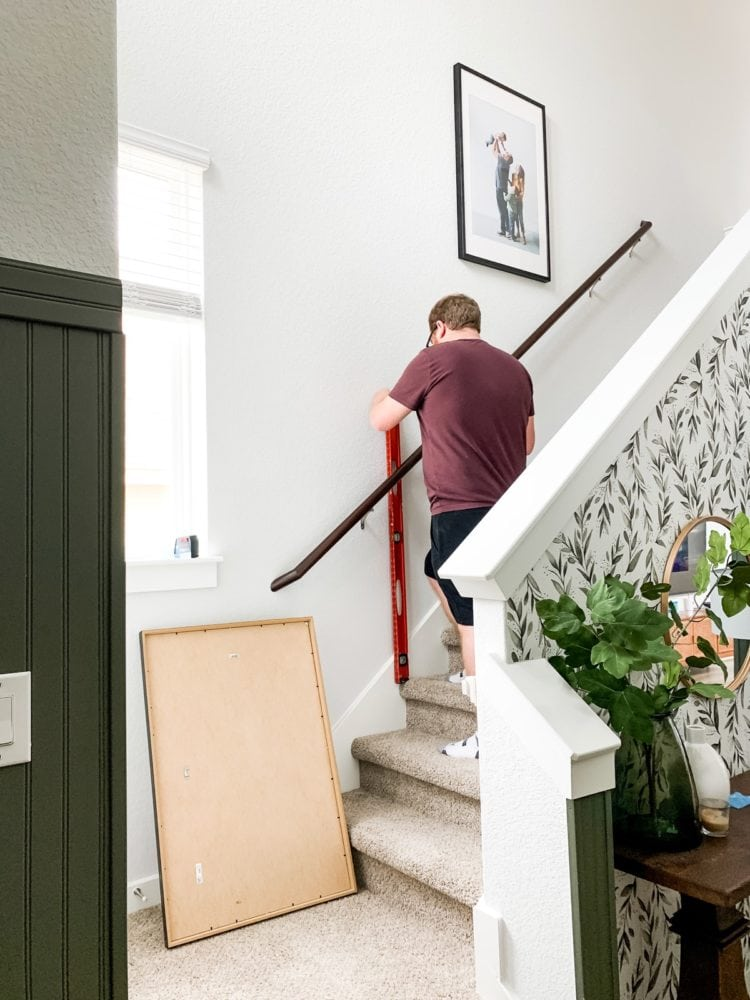 Man measuring to hang photos on a stairwell