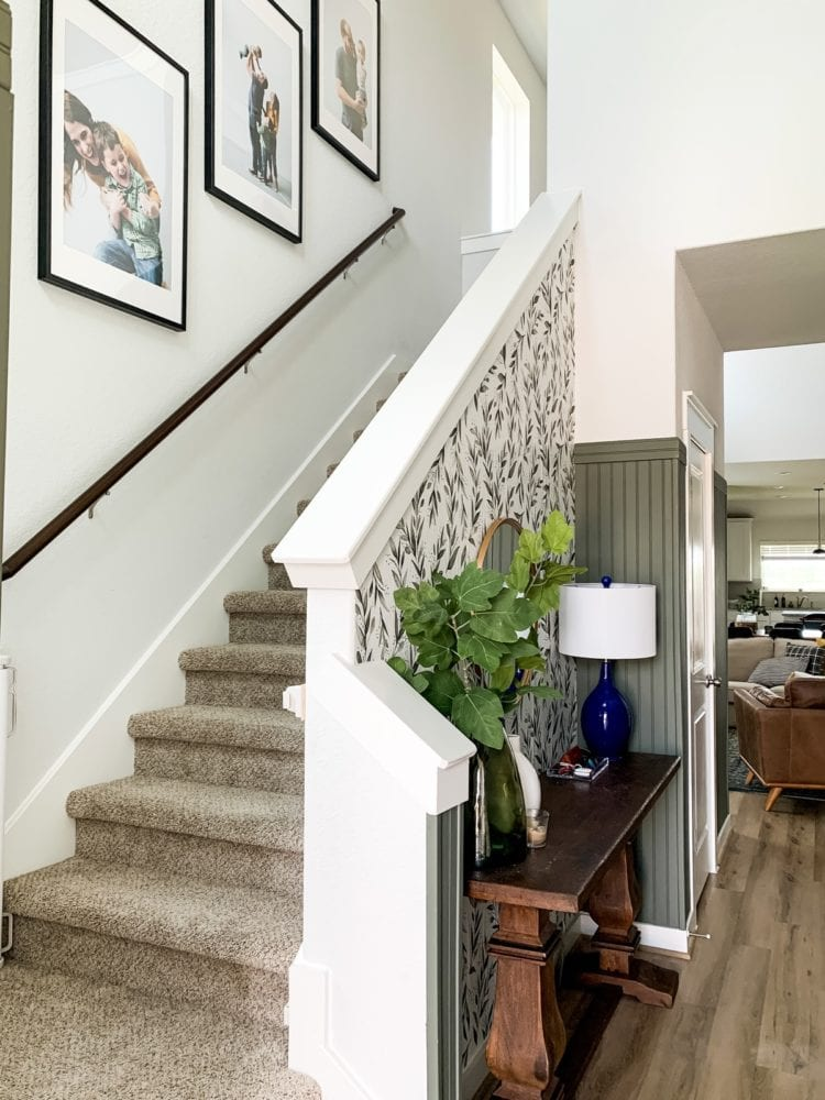 staircase with wallpaper and large prints