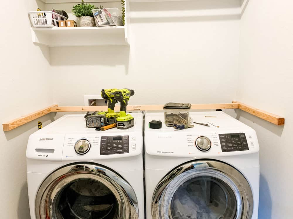 Side by side washer and dryer with ledger boards installed into walls for laundry room countertop