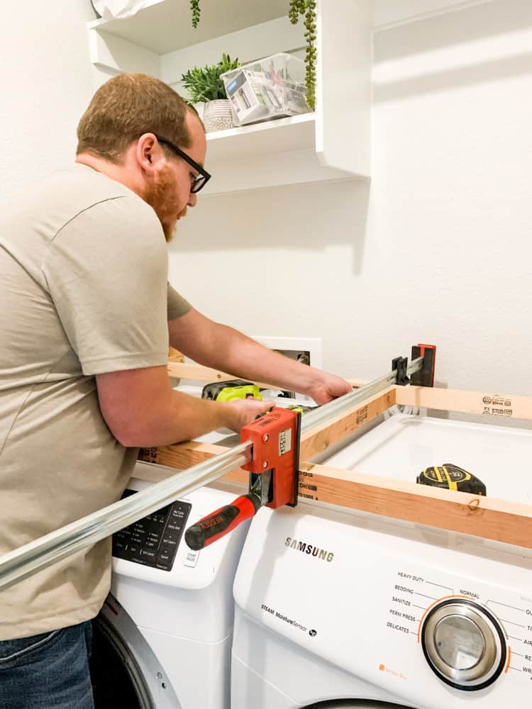 Man installing supports for laundry room countertop
