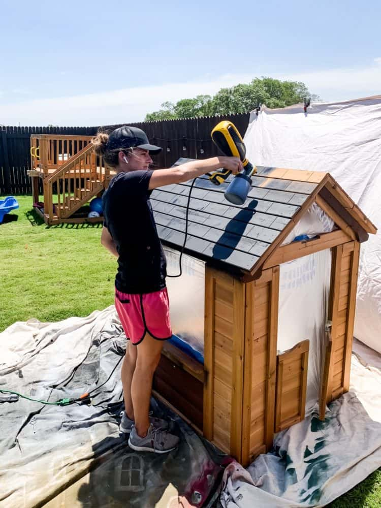 woman painting a playhouse with a paint sprayer