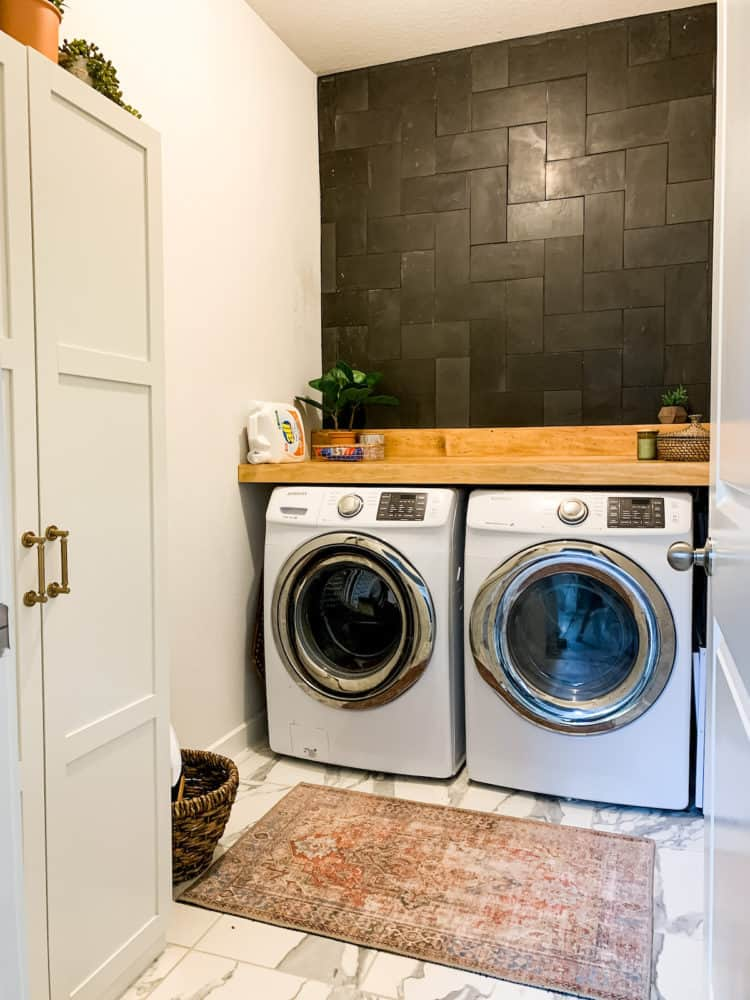 Laundry room with a tiled basalt wall