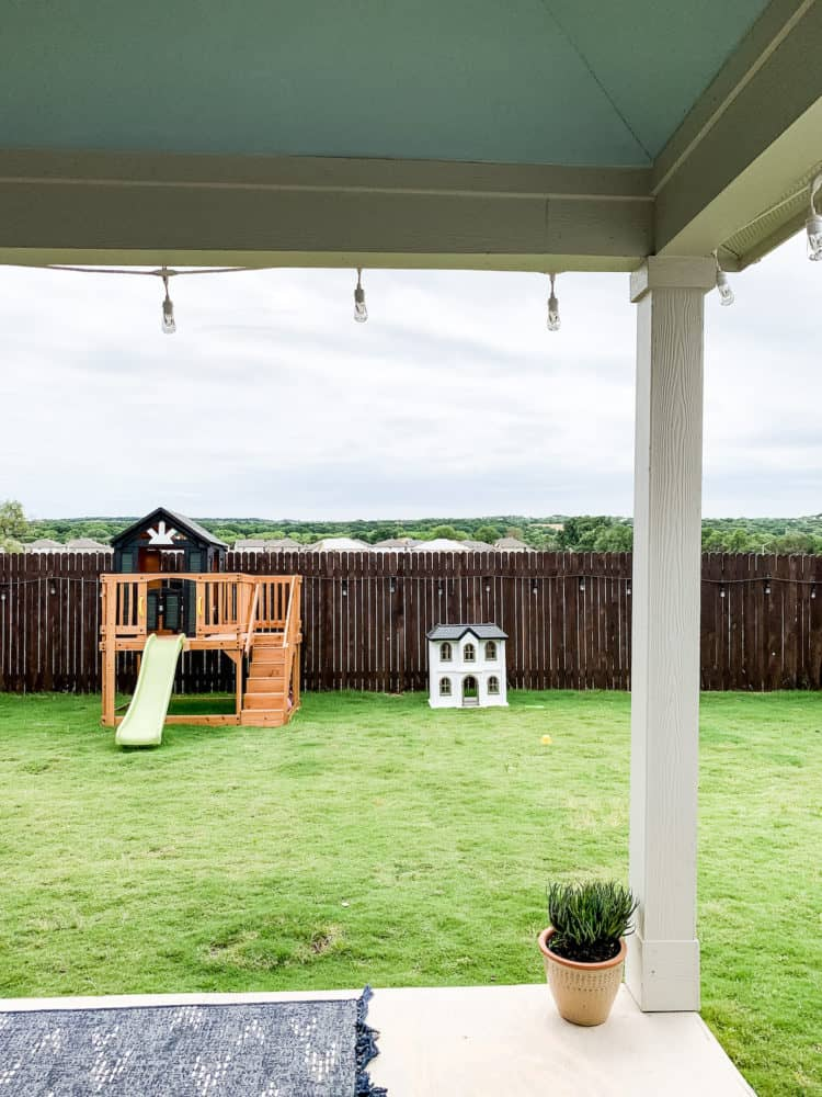 an adorable backyard with kids toys and a blue porch ceiling