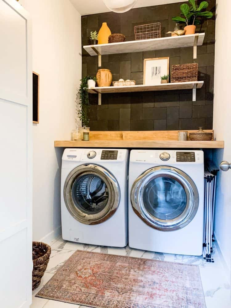 Laundry room with black tiled wall