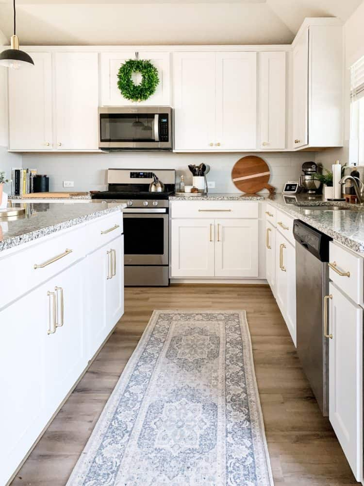 A white and gray kitchen with gold cabinet hardware