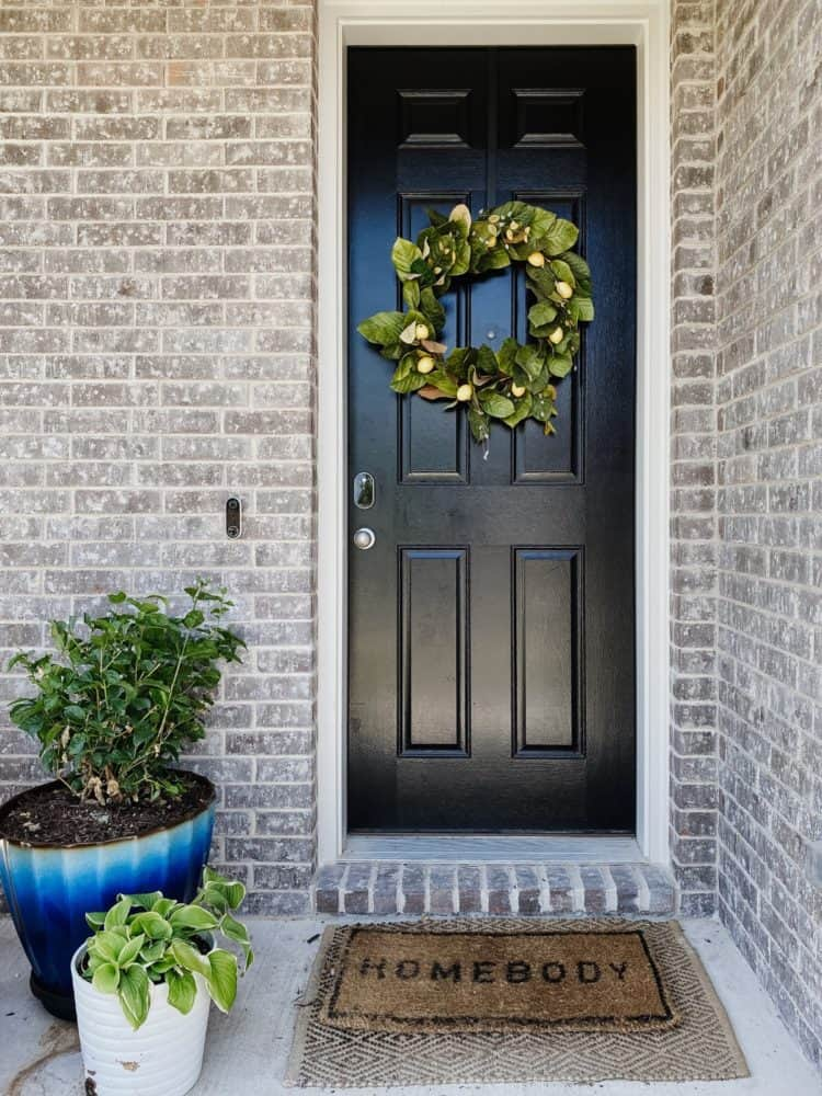 front porch with a faux wreath and potted plants
