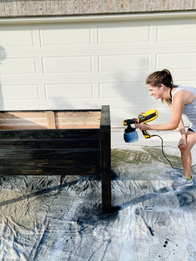 woman staining a garden bed with a paint sprayer