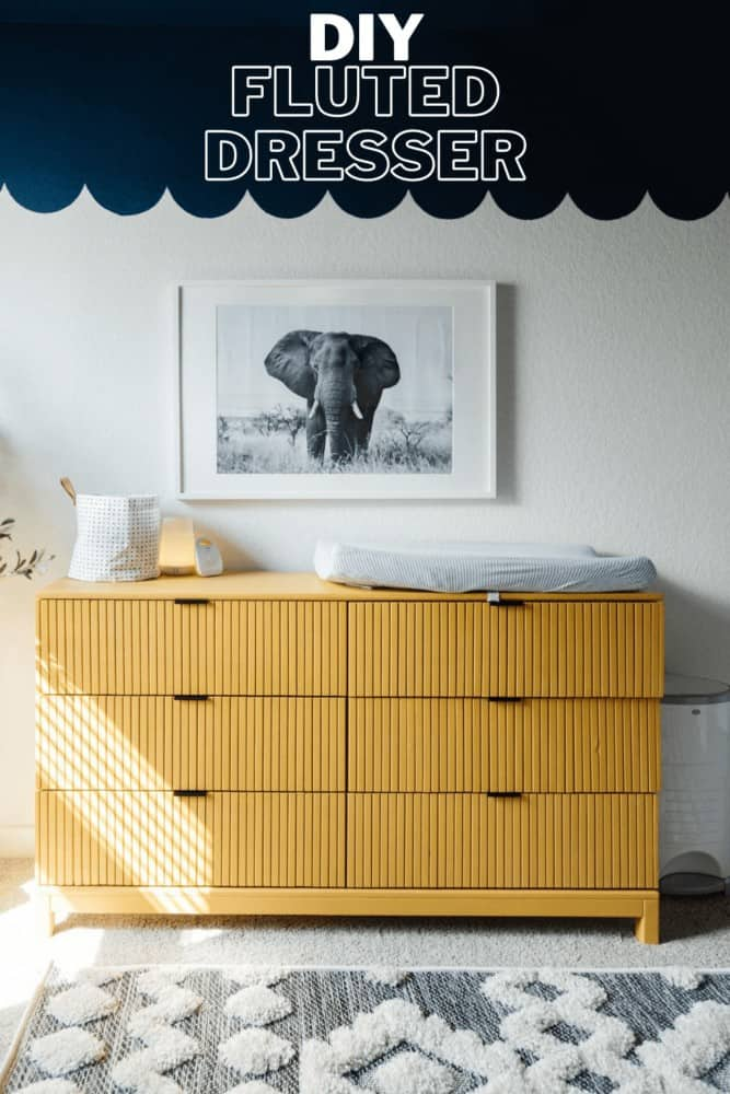 vertical image of an IKEA TARVA dresser that has had trim added to it and has been painted yellow. It's styled with an elephant art print above it and has a text overlay - diy fluted dresser