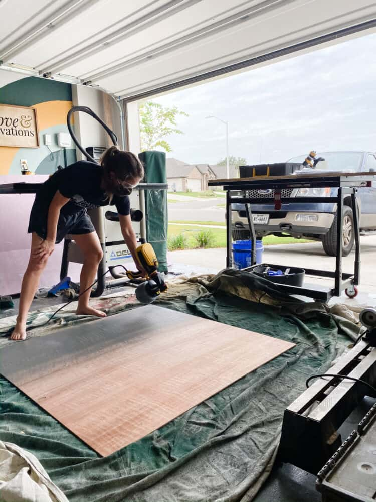 woman painting a large sheet of plywood using a paint sprayer