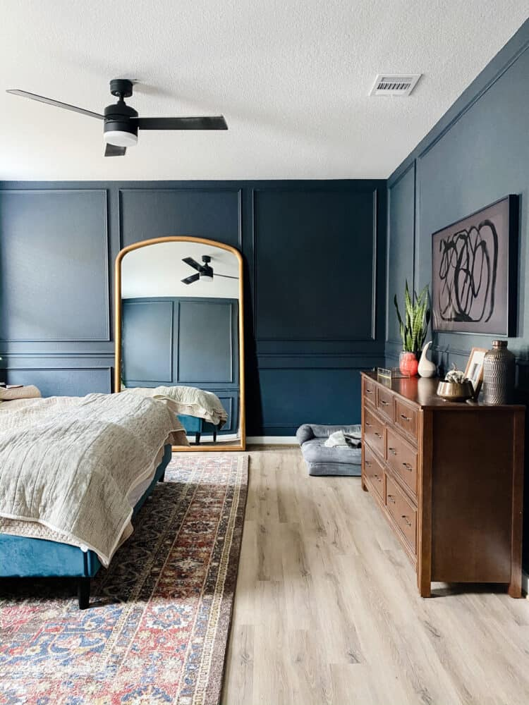 a dark blue bedroom with trim on the walls, a large mirror, and a wall-mounted television with hidden cords
