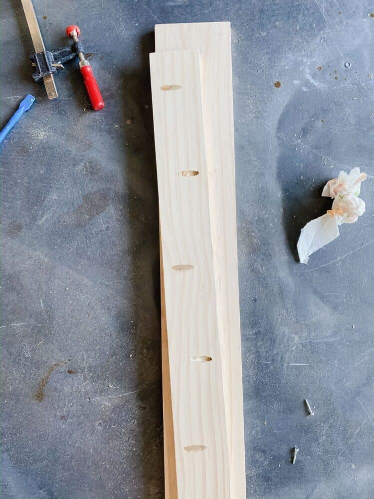 A 1x4 pine board with pocket holes drilled along each side of it.