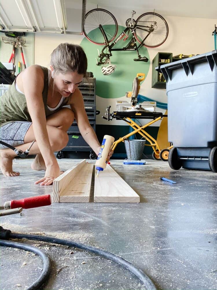 Woman adding wood glue to a board for the back of a DIY art ledge