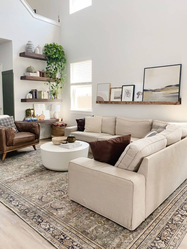 a neutral living room with floating shelves and a large art ledge
