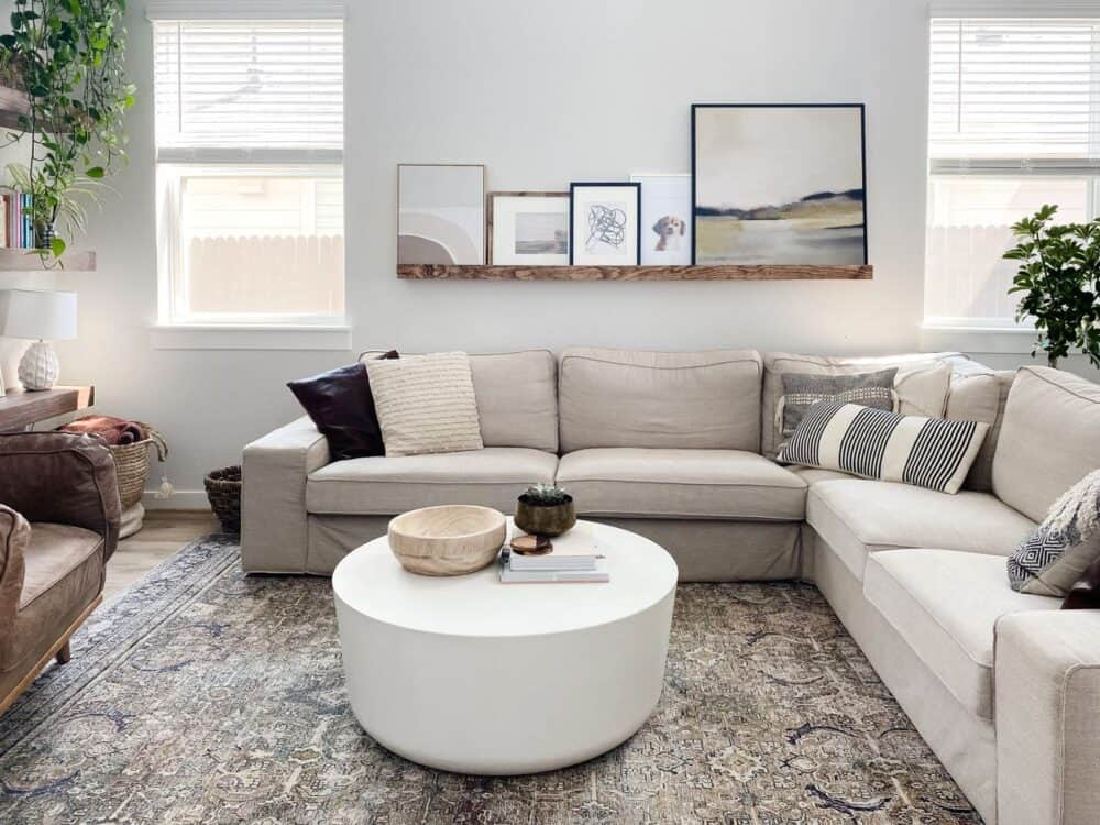 a neutral living room with a white coffee table and a DIY art ledge