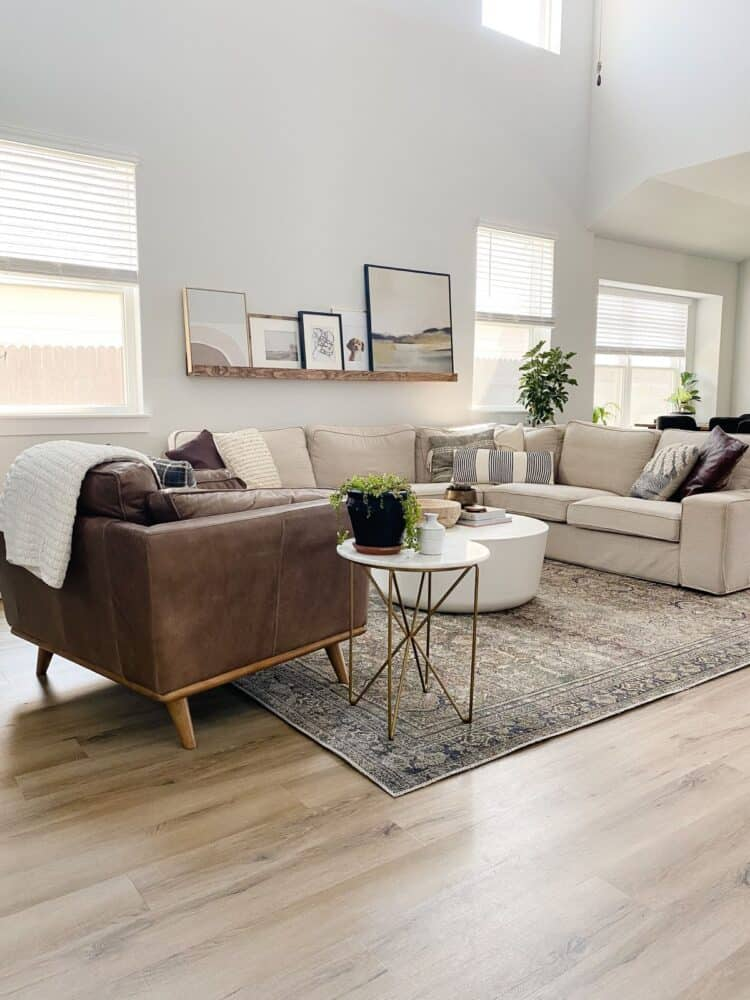 living room with a large sectional with an art ledge hanging above it