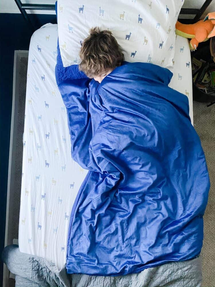 A young boy sleeping with a weighted blanket