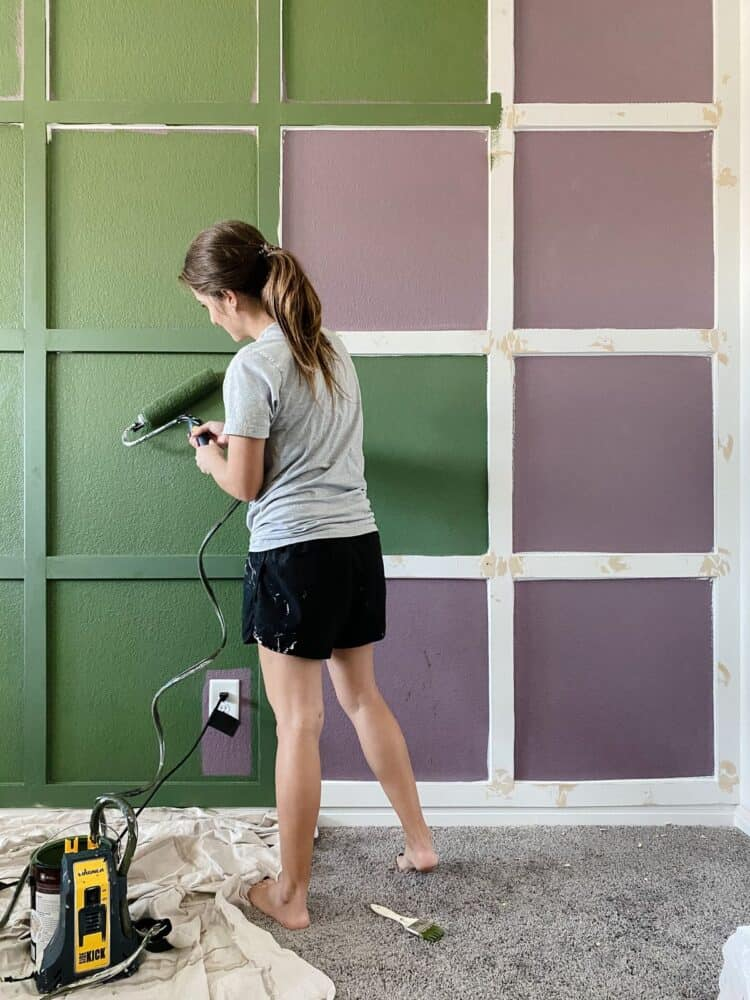 woman painting a wall using a power roller