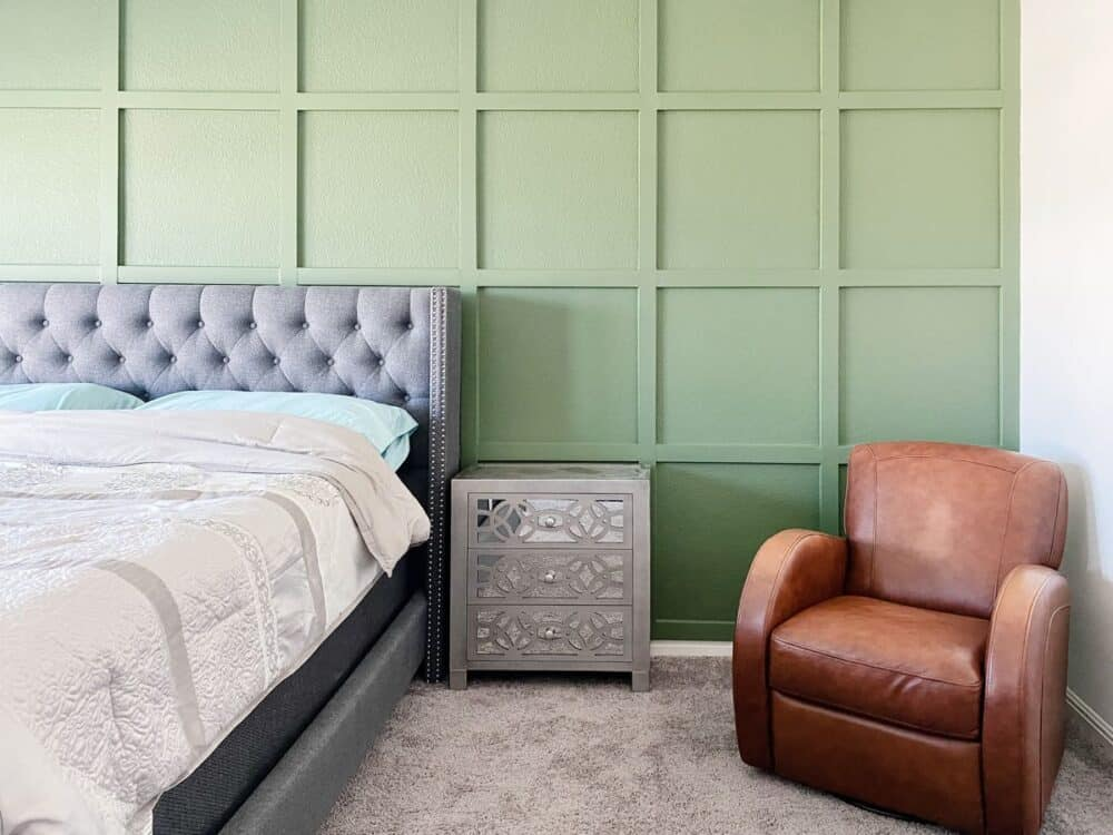 A bedroom with a green accent wall