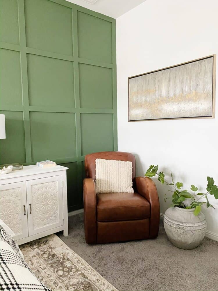 corner of a green and white bedroom with a leather chair, art, and a large vase