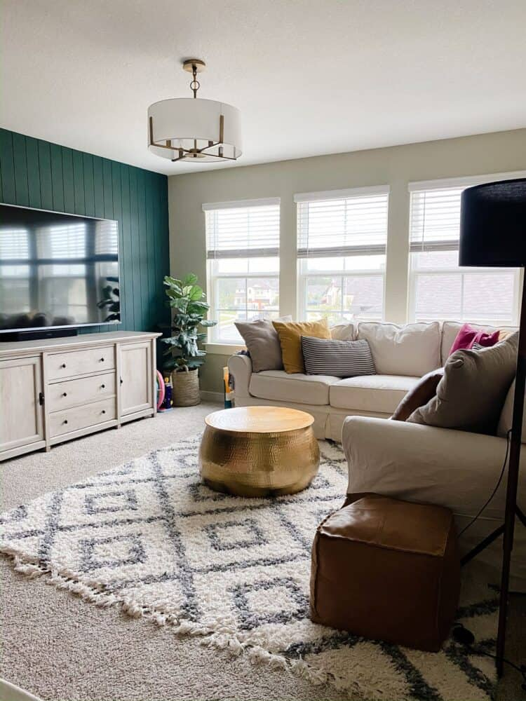 kid's game room with neutral furniture and a green accent wall