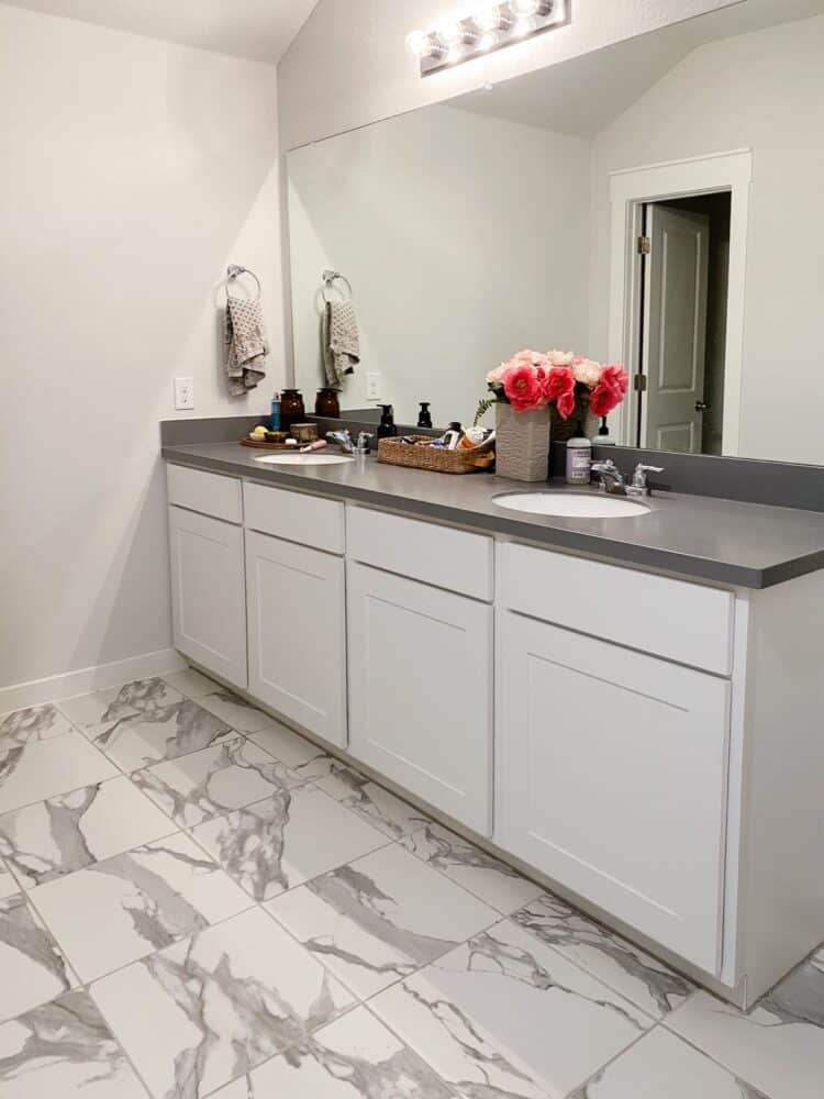 A gray and white master bathroom with an extra long vanity