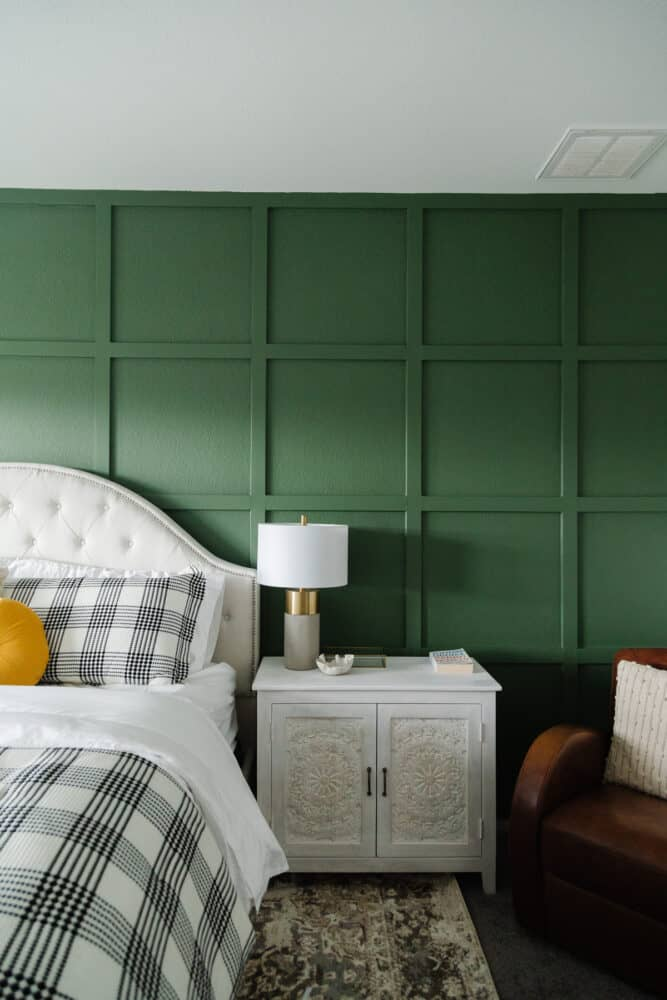 grid accent wall with a white headboard and nightstands